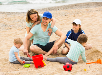 parents with  children playing in the sand