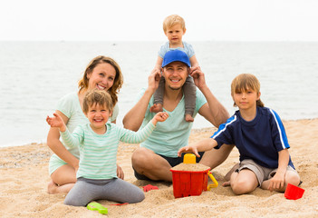 Happy family of five at sea shore
