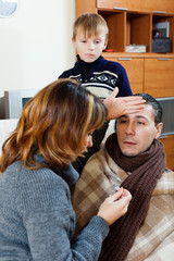 Sick man surrounded by caring wife and son
