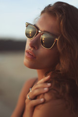 Young beautiful curly woman in sunglasses at the seaside