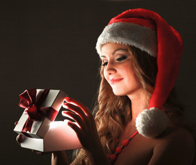 Close-up of woman with gift isolated on black background