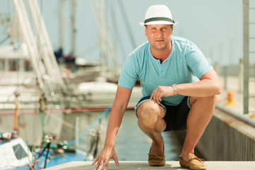 Fashion portrait of handsome man on pier against yachts