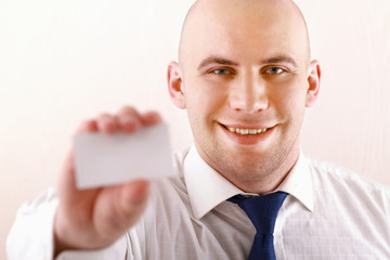 Portrait of young  businessman holding blank white business card
