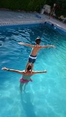 Niño haciendo equilibrio en la piscina
