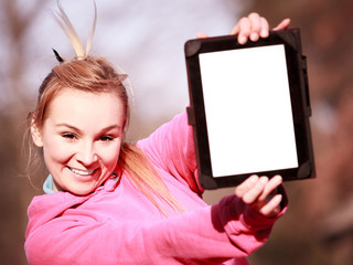 Woman teenage girl in pink tracksuit showing tablet