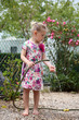 Little girl playing with water hose in the garden