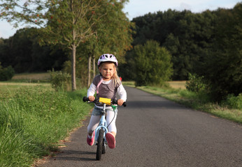 Little girl riding her training bike outdoors