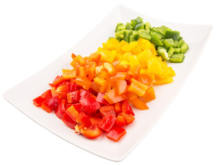 Colorful chopped capsicums in a plate over white background
