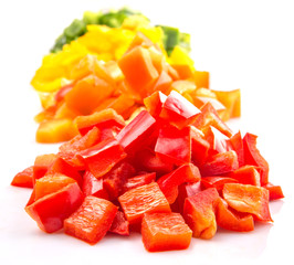 Heaps of chopped colorful capsicums over white background