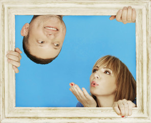 Couple Behind Wooden Frame on Sky Blue Background