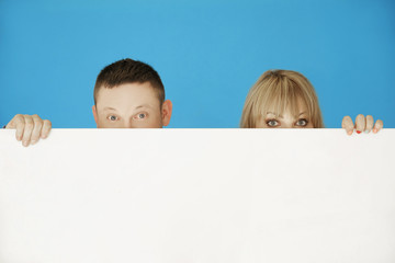 Two Young Couple Hiding on White Wall
