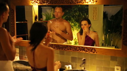 Young couple applying cosmetics in luxury bathroom at night