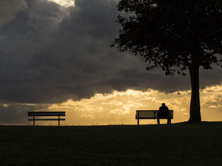 Silhouette of an anonymous man alone on a bench at sunset