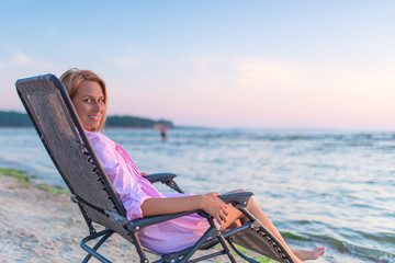 woman sitting in chair near a ocean