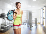 Fototapety Young Woman in sport wear with bag in gym