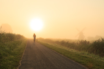 Cycling in the fog during a summer sunrise.