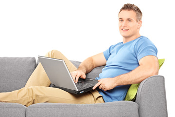 Young man relaxing with a computer seated on sofa