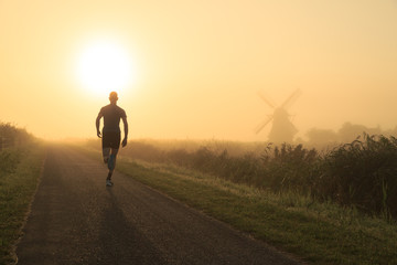 Man running in the foggy countryside