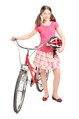 Teenage girl holding a helmet and pushing a bike