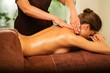 Beautiful young woman having massage in a spa salon