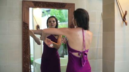 Woman applying antiperspirant deodorant in front of the mirror