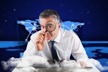 Composite image of mature businessman examining with magnifying