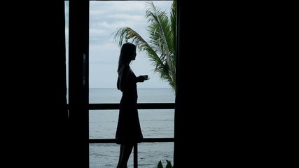 Silhouette of woman drinking coffee on terrace with view at sea