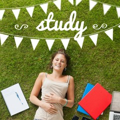 Study against pretty student lying on grass