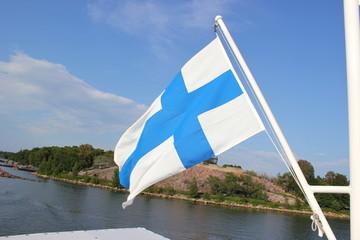 Die finnische Blaukreuzflagge vor einer Schäre bei Helsinki