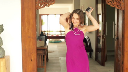 Happy woman listening to music and dancing in luxury villa