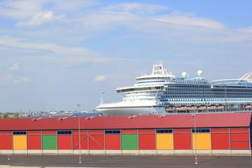 Bunte Garagen vor einem Passagierschiff im Hafen von Tallinn