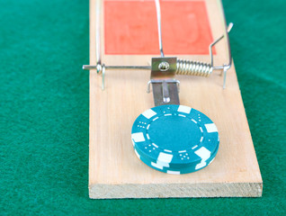 Mousetrap and casino chip on green background
