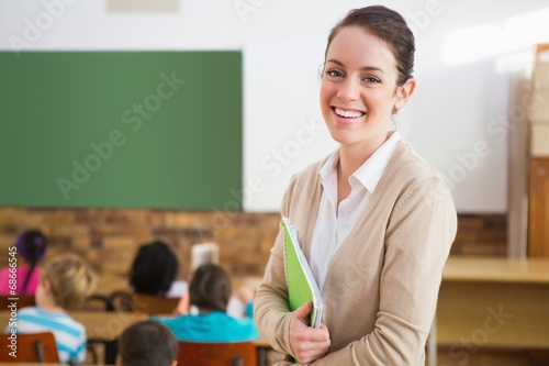 Leinwanddruck Bild Pretty teacher smiling at camera at back of classroom