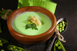 Tasty peas soup on wooden table with dark light