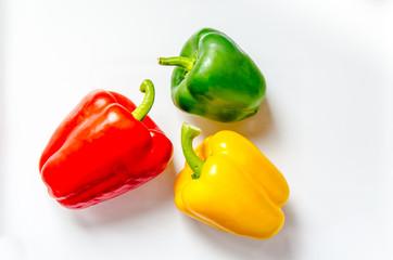 Paprika rot gelb gruen nebeneinander auf weiss