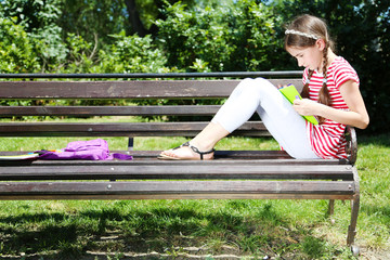 Cute girl drawing on bench in park