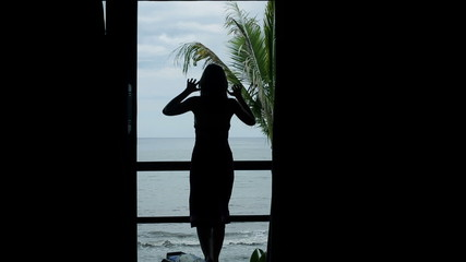 Woman unveil curtains, stretching on terrace with view at sea