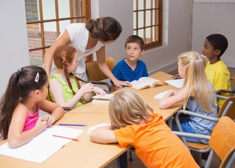 Pretty teacher standing with pupils at desk