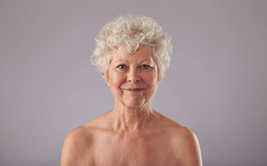 Beautiful senior woman shirtless against grey background