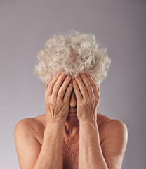 Sad senior woman covering her face