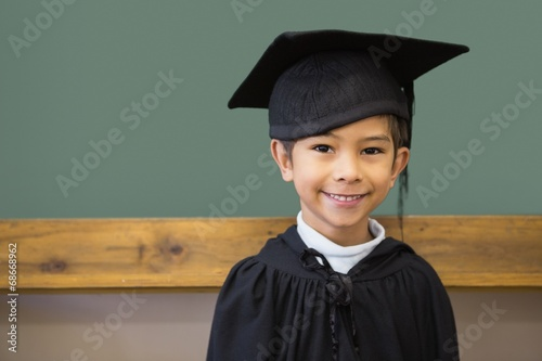 Papiers peints Table preparee Cute pupil in graduation robe smiling at camera in classroom