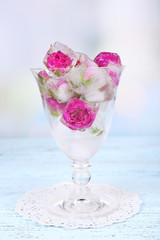 Ice cubes with rose flowers in glass bowl on light background