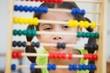 Leinwandbild Motiv Cute pupil using abacus in classroom