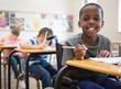 Disabled pupil smiling at camera in classroom - 68669981