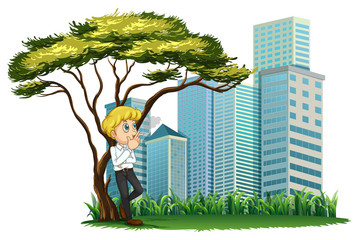 A man smoking under the tree across the buildings