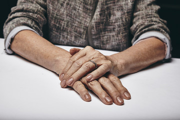 Old woman's hands resting on grey surface
