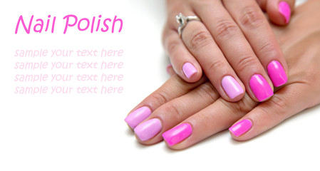 Women's hands with a colored pink nail polish with sample text