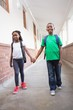 Cute pupils holding hands in corridor