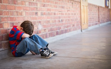 Sad pupil sitting alone in corridor
