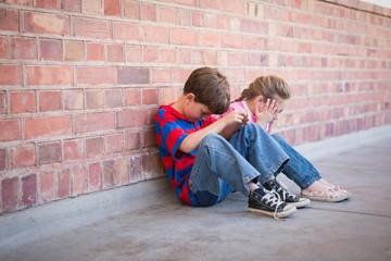 Sad pupils sitting in corridor